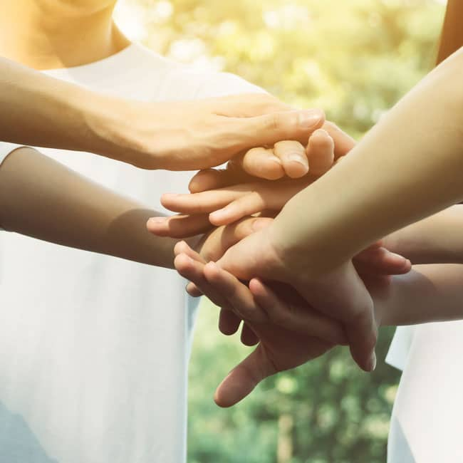 Group of people placing hands on top of each other