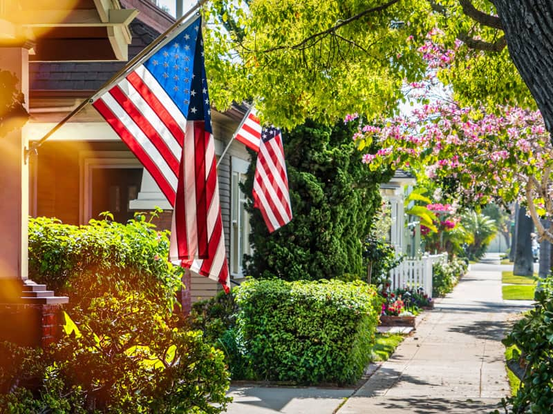 Quiet neighborhood street with American flags hanging prominently
